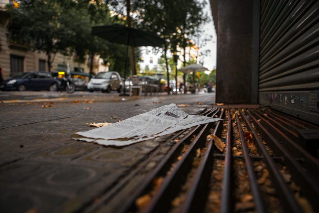 A page of newspaper is discarded on a street.