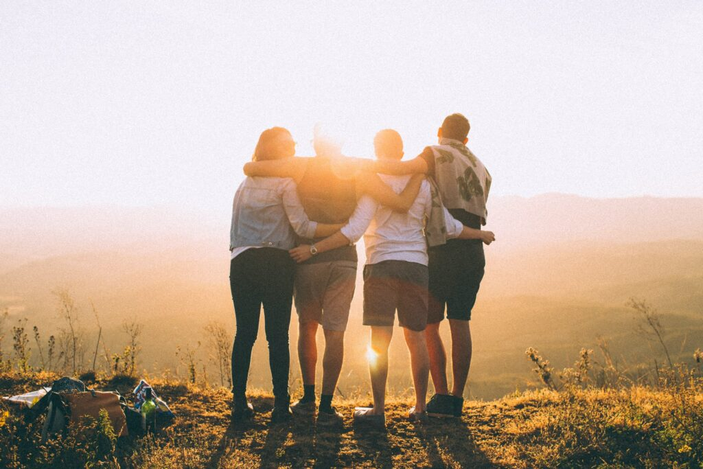 Friends hugging and watching a sunset.