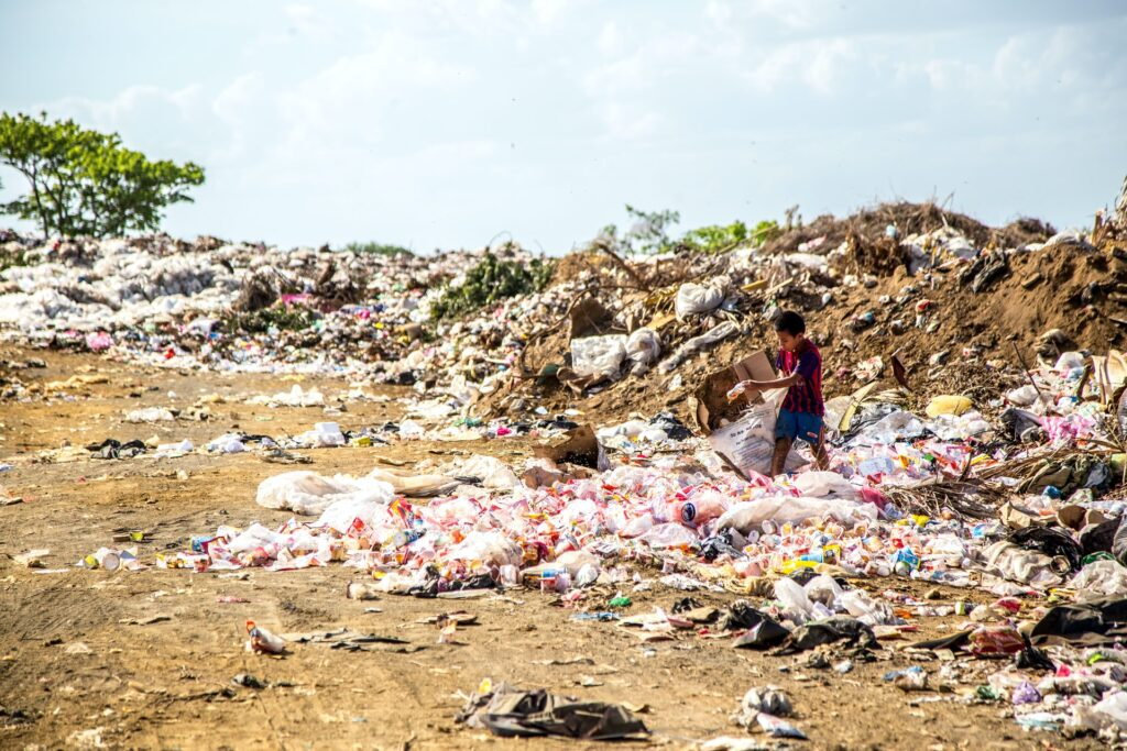 A child sorts through mounds of garbage and recycling.