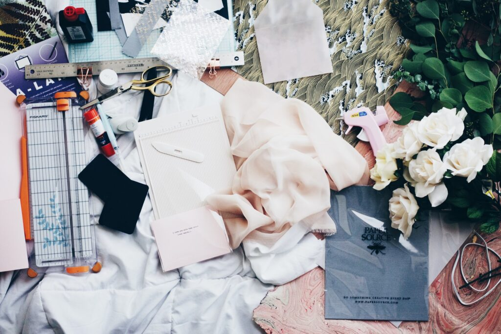 Fabric scraps and other assorted D.I.Y. items sprawled across a table top.