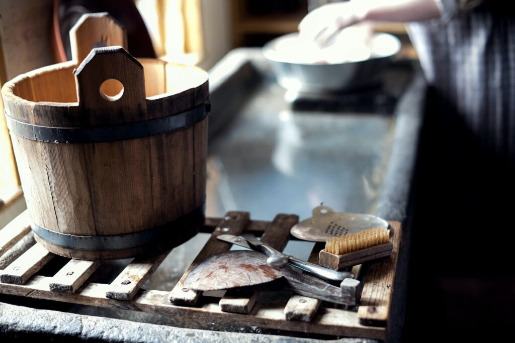 A wooden bucket is beside a sink used for washing.